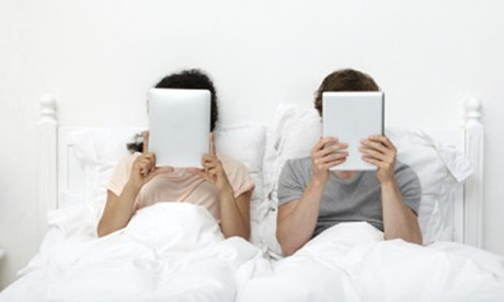 Couple in bed with iPads